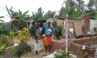 Rita and one of her children standing in front of her house