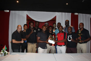 Captain of the Colts Basketball team Dave Causway (centre) is all smiles as he receives the tourney winnings from Mackeson Brand Manager Jamaal Douglas while other members of the team look on and display their respective accolades