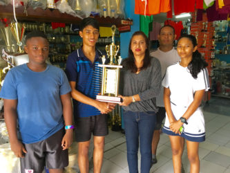 Ms. Devi Sunich of Trophy Stall, Junior Sportsman of the year Narayan Ramdhani, GBA Rep Marlon Chung and some Junior Players display some of the trophies that are up for grabs.