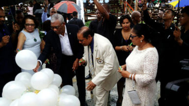 President David Granger and Prime Minister Moses Nagamootoo along with their spouses writing their personal commitments to the promotion of social cohesion on white helium filled balloons, which were later released. (OPM Photo)
