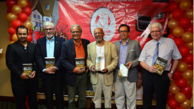 Minister of Education Dr. Rupert Roopnarine and author of the History of Guyana Cricket Professor Clem Seecharan (both center) share a photo with other distinguished guest during Friday's book launching. (Orlando Charles photo)