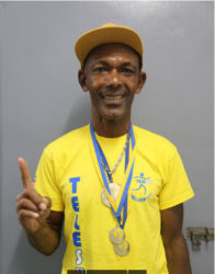 Marathon stalwart Llewellyn Gardner posing with his spoils following his exploits at the Telesur 10 kilometre events in Suriname earlier this month.