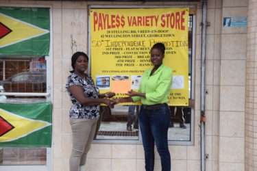 Payless Variety Store's representative, Shonel Blackman presents a sponsorship cheque to one of the organizers, Avril Black yesterday in front of the Robb and Charlotte Streets entity.