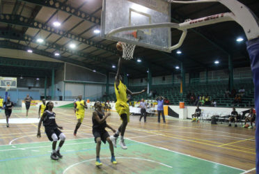Andrew Johnson of Plaisance Secondary in the process of scoring a layup during his team's matchup with Tutorial High at the Cliff Anderson Sports Hall