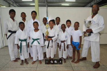 Sensei Winston Dunbar and Sadella Britton holding trophies, with some of the participants.