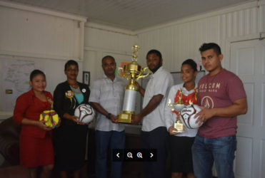 Deputy Regional Executive Officer (DREO) for Region 8, Gavin Gounga receiving the Championship trophy from Coordinator of the competitions, Harold Waqar Shiwnarain with officials of the RDC and some teams' representatives looking on.