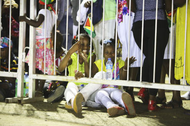 Two children enjoying their seats on the ground as the stands could not accommodate them.