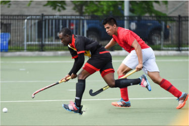 Guyana's Aroydy Branford in the act to receive the ball while being pursued by his Mexico marker during their matchup in the Pan American Junior Hockey Championships at the University of Toronto Facility