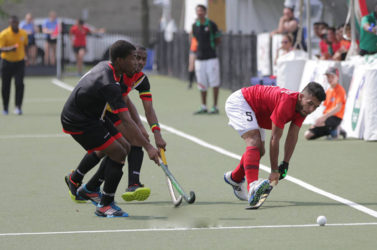 Guyana's Kareem McKenzie (left) and Mark Sergeant in the process of challenging a Mexican player for the ball during their 5-8 Positional Tourney match at the University of Toronto Facility in the Pan American Junior Hockey Championships
