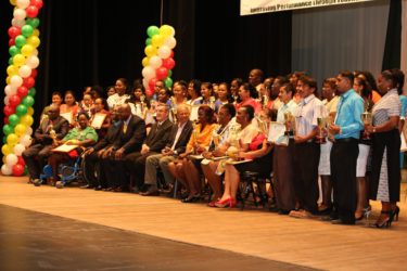 The awardees yesterday after the ceremony held in their honour, posing with their trophies and plaques. Seated among them in the front row are (beginning fourth from left) Chief Education Officer Olato Sam, Director of School of the Nations Dr Brian O'Toole, and Minister of Education Dr Rupert Roopnaraine. (Photo by Keno George)