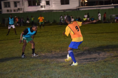 Job Caesar of Cross Street (left) trying to maintain possession of the ball while being challenged by an Old School Ballers defender during their matchup at the Santos Training Area in the Ministry of Health/Petra Soft Shoe Championship.