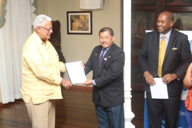 Minister of Agriculture Noel Holder (left) receiving the draft legislation from Minister of Indigenous Peoples' Affairs Sydney Allicock (centre) with attorney Nigel Hughes (right)