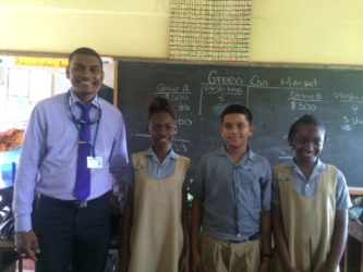 Solid Waste Director Walter Narine (left) and the environmental prefects at St Pius Primary