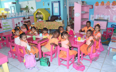 Nursery School students enjoying their snack of biscuits and juice as part of the national School Feeding Programme. (Photo courtesy of Ministry of Education)