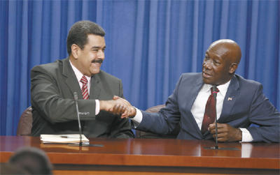 Venezuelan President Nicolas Maduro, left, and Prime Minister Dr Keith Rowley exchange a handshake during a joint press conference following bilateral talks at the Diplomatic Centre, St Ann's, yesterday.