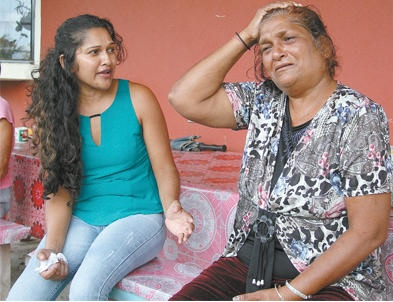Flora Siewnarine, right, recounts the incident which led to the death of her son, Sham, at her home in Gopee Trace, Penal, yesterday.