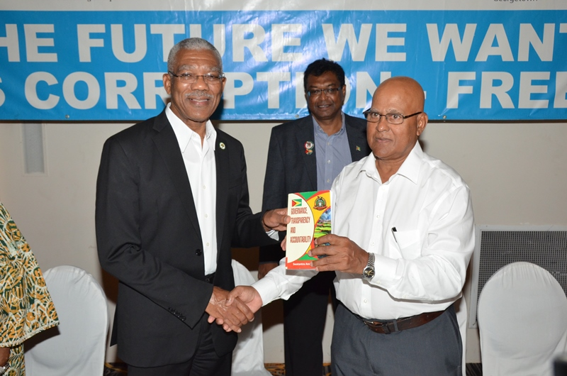 President David Granger (left) receives a copy of the book from Dr. Anand Goolsarran as Vice President and Minister of Public Security, Khemraj Ramjattan looks on. (Ministry of the Presidency photo)