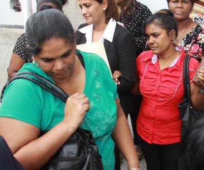 Donna Francis, left, estranged wife of David Francis, passes common-law wife, Chandrawatie Nandlal, outside the San Fernando High Court after yesterday's ruling.