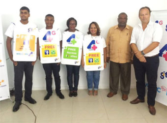 GTT Chief Commercial Officer Gert Post (right) and Ministry of Public Telecommunications Permanent Secretary, Derrick Cummings (second from right) with GTT employees advertising the new features.