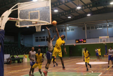Nigel Bowen of Plaisance Secondary scores a layup while being challenged by a St. Stanislaus College player during their matchup in the U19 section of the National Schools Basketball Festival Georgetown and East Coast Regionals at the Cliff Anderson Sports Hall recently.