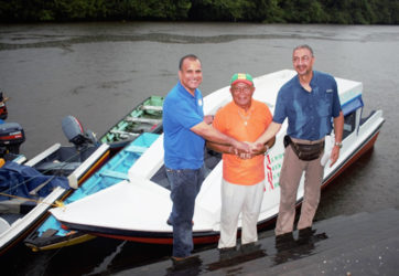 From left are CEO of Food for the Poor (Guyana) Kent Vincent, Toshao James Miguel and Managing Director of Courts Clyde De Haas during the handing over of a water ambulance intended to serve St Monica and Karawab. In the background is the new vessel.