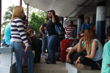 Venezuelan nationals wait to board a boat at Cedros before checking in with Immigration officials last Wednesday.