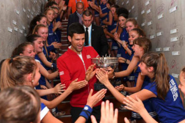 French Open champion Novak Djokovic celebrates with the ball girls. (Reuters photo)