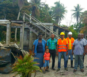 Fredrick James (second, right) with Amar Chetram and his brother (in construction vests), Vladimir Glasgow (second, left) and Mrs James (left) in front of the burnt house.