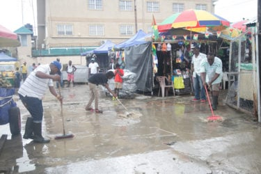 Parliament View Mall vendors yesterday morning trying to remove water lodged in their vending space following rainfall overnight. (Photo by Keno George) (See story on page 9)