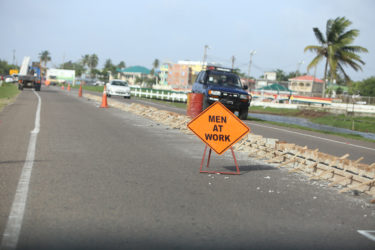 Another sign and cones in the background lining the construction in the middle of the road.