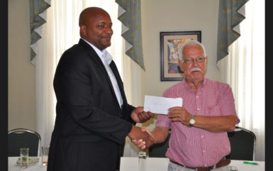 Former GABF President Joseph 'Reds' Perreira (right) handing over his donation to current GABF Chief Nigel Hinds following the conclusion of the press event staged at the Cara Lodge Hotel Monday.