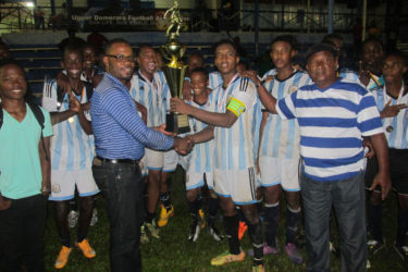 Victorious captain Javair Smith collecting the championship trophy from UDFA President Sharma Solomon while other members of the team look on after defeating Amelia's Ward Panthers in the finale at the Mackenzie Sports Club ground