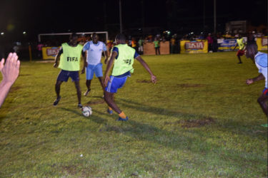 Akeem Saul (right) of Holmes Street Tiger Bay in the process of completing a pass to team mate Jamal Blackman (left) while Dennis Edwards (centre) of Sparta Boss pursues during their matchup in the Ministry of Health/Petra Organization Soft Shoe Championship at the Parade ground