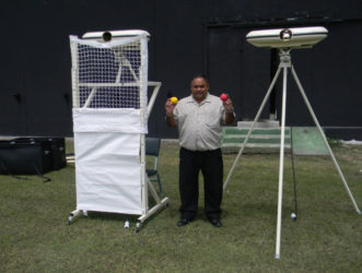 Guyana Cricket Board president and CGI executive Drubahadur shows off the local franchise's new bowling machines.