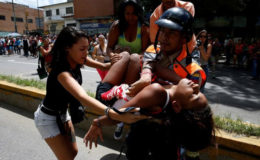 A police officer carries a woman who fainted while gathering to try to buy pasta outside a supermarket in Caracas, Venezuela, June 10, 2016. REUTERS/Carlos Garcia Rawlins/File Photo