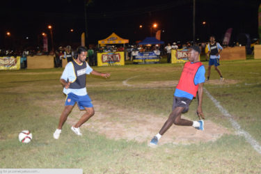Darren Benjamin (right) of Broad Street completing a pass while being challenged by West Front Road's Nathaniel Nagaloo during their matchup in the Ministry of Heath/Petra Organization soft shoe championships at the Santos Training Area.