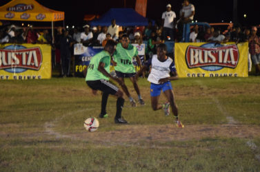 Albouystown's Lennox Cort (right/white) evading the challenge of Dennis Edwards of Tucville (left/green) in their high scoring drawn encounter at the Santos Training Area in the in the Ministry of Heath/Petra Organization soft shoe championships.