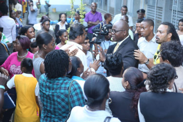 Chief Education Officer Olato Sam (right of centre with glasses) was bombarded with questions from irate parents during the meeting held yesterday to discuss the temporary closure of the Brickdam Secondary School.  (Keno George photo)
