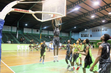 GTI's Roger John in the process of dunking against the Bishops' High during their u-19 quarterfinal matchup at the Cliff Anderson Sports Hall.
