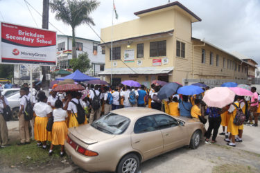 Students and their parents gathered in front of the Brickdam Secondary School to collect relocation letters yesterday morning. (Photo by Keno George)