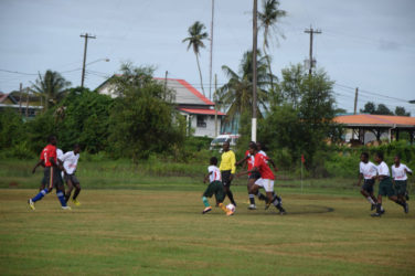Action between Canje Secondary (red) and Overwinning in the Digicel Secondary Schools Football Championships at the Burnham park ground in Berbice yesterday.