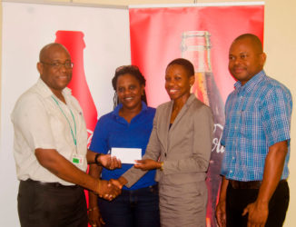 Former Olympian Aliann Pompey receives the sponsorship cheque from Brand Manager Clive Pellew while meet official Mayfield Taylor-Trim and Banks DIH's Kester Van-Nooten look on.