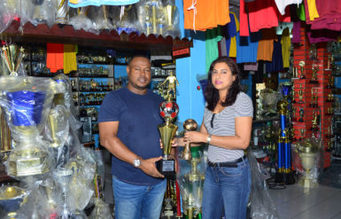 Petra Organization Co-Director Troy Mendonca collecting the trophies from Trophy Stall representative Devi Sunich yesterday.