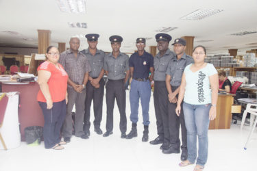 Five of the six firemen who were injured as a result of the Gafoors fire pose with representatives of the company, including Finance Director Michael Daniels (second left) shortly after receiving their cheques.