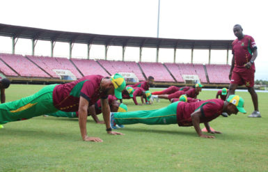Strength and conditioning trainer Clinton Jeremiah looks on as members of the Guyana Amazon Warriors team engage in some planking as part of their first day of training camp yesterday at Providence.