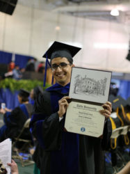 Daniel Ram holds up his Phd in Immunology