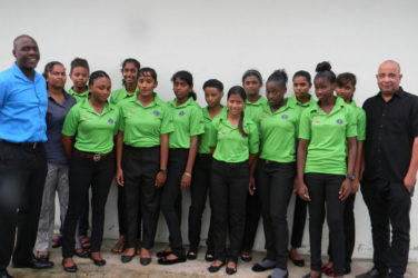 Members of the Guyana U-19 girls team pose for a photograph with Chief Executive Officer of Top Brandz Distributors, Wayne James (right) and Technical Development Officer of the Guyana Cricket Board, Colin Stuart (left) manager, Devika Gobin (2nd left). Captain Plaffianna Millington is first from left front row).