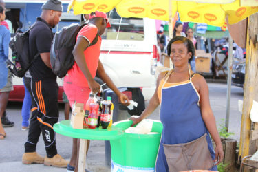 Maylene Innis with her water cooler selling at the junction of Regent and Wellington streets (Photo by Keno George)