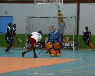 Old Fort's Aderemi Simon unleashing a powerful shot which was denied by GCC's Stephen Xavier (behind the goalkeeper) during their matchup at the National Gymnasium.