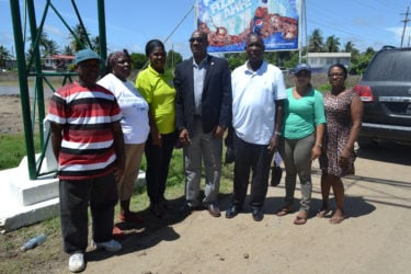 Minister of State,  Joseph Harmon (centre) with Chairman of the Lancaster/Hogstye NDC Forbes Moore (third from right) along with other members of the community during one of his visits to East Berbice-Corentyne. (Ministry of the Presidency photo)